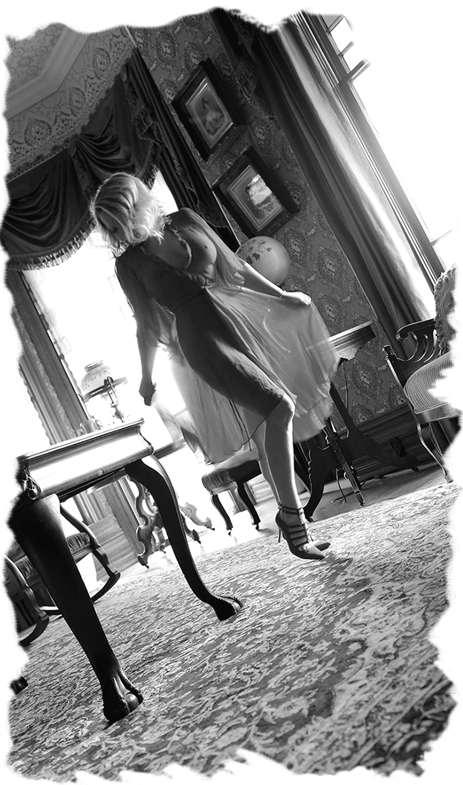 Nashville Escort Megan Love in a black and white photo, wearing a sexy sheer dress inside of an elegant Victorian-styled room