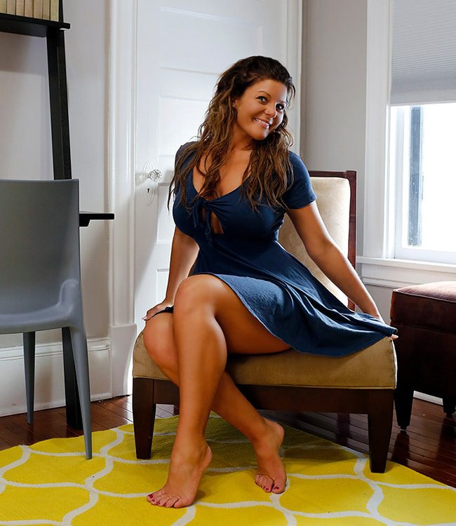 Kali, Minneapolis Escort - sitting in chair wearing blue dress