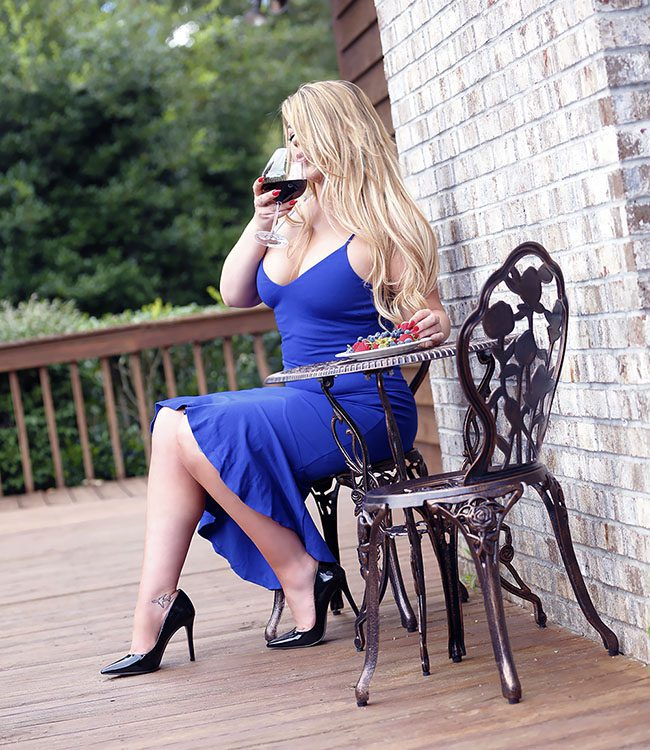 Alexis Jorden, Minneapolis Escort, sitting at table on a wood deck, wearing a blue dress, sipping wine and eating fruit
