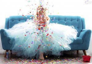 Megan Love sitting on blue couch wearing a tutu and throwing confetti