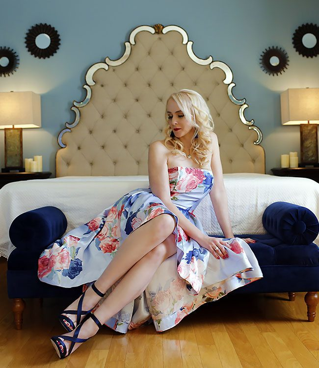 Claire Carraway sitting at the end of a bed wearing a floral dress