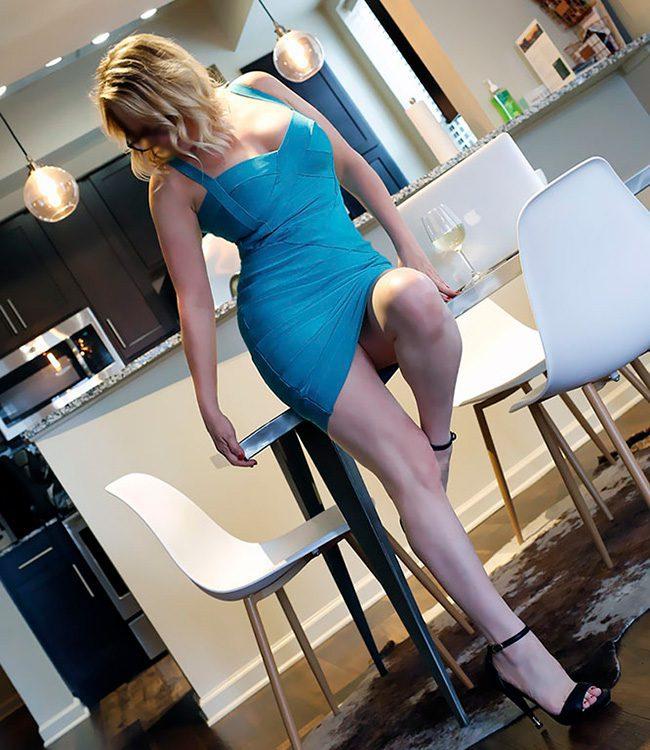 Megan Love, Raleigh escort, posing is a sexy blue short skirt