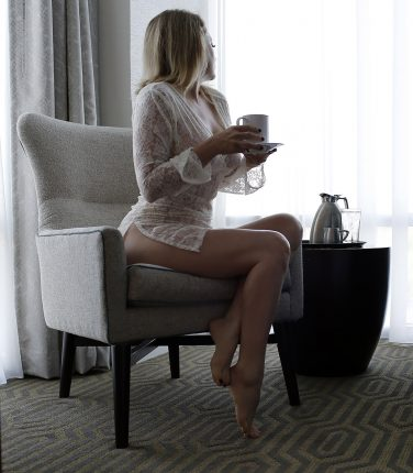 Megan Love sitting in a chair drinking coffee, wearing a white sheer blouse