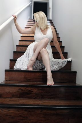 Megan Love in white dress on stairs