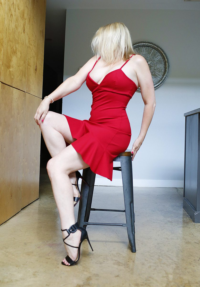 Megan Love sitting on a stool in a sexy red dress