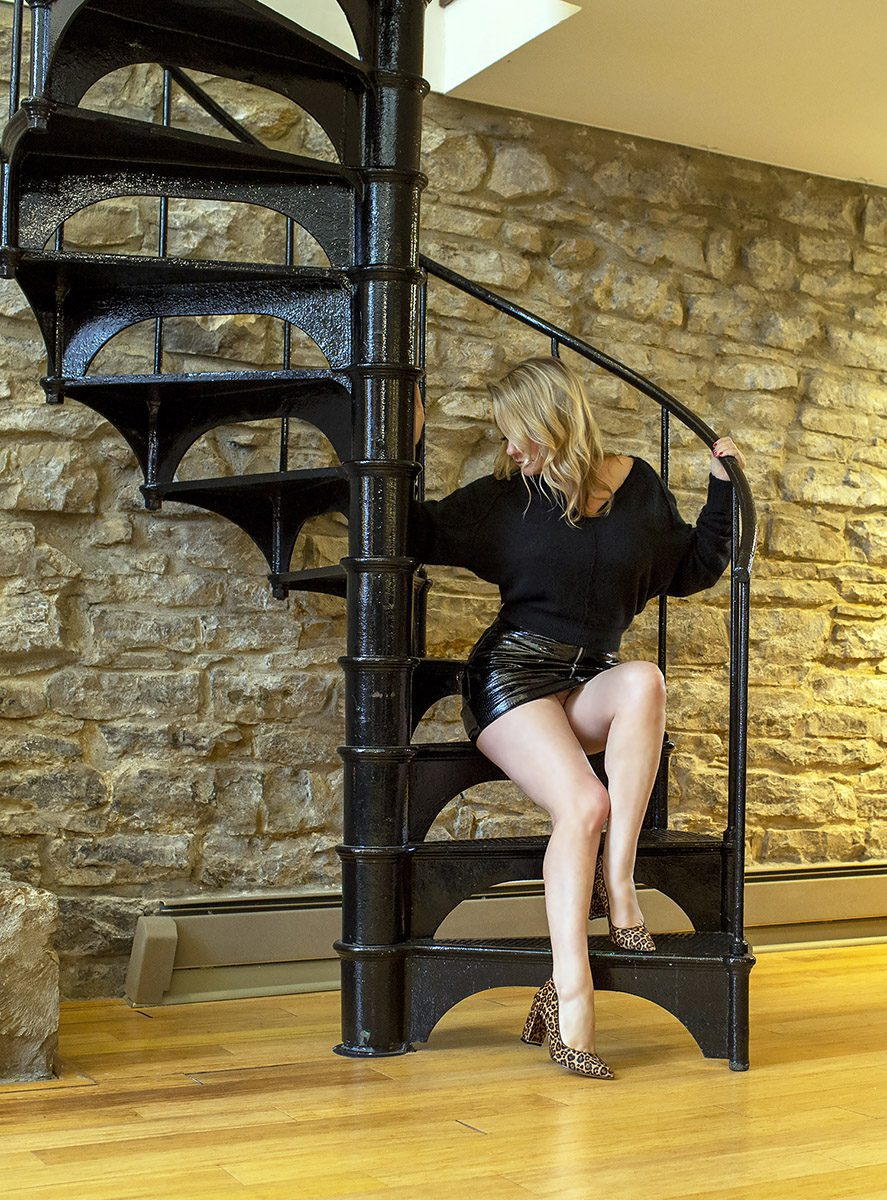 Megan Love wearing a short black skirt sitting on a spiral staircase