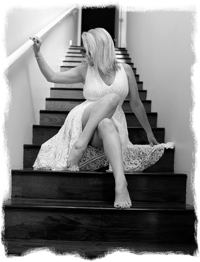 Megan Love, a Nashville escort in a white dress sitting on steps
