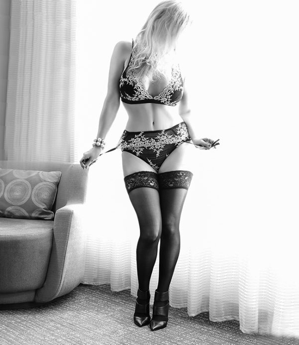 Megan Love, female escort in a black and white image, wearing a sexy outfit