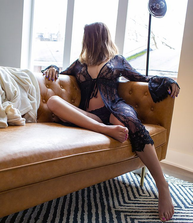 Tanya Delight, Nashville escort wearing black lingerie sitting on a leather sofa