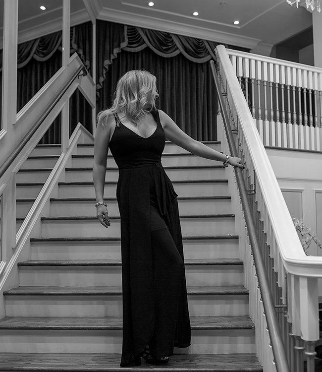 Megan Love, Charlotte Escort in black dress standing on staircase